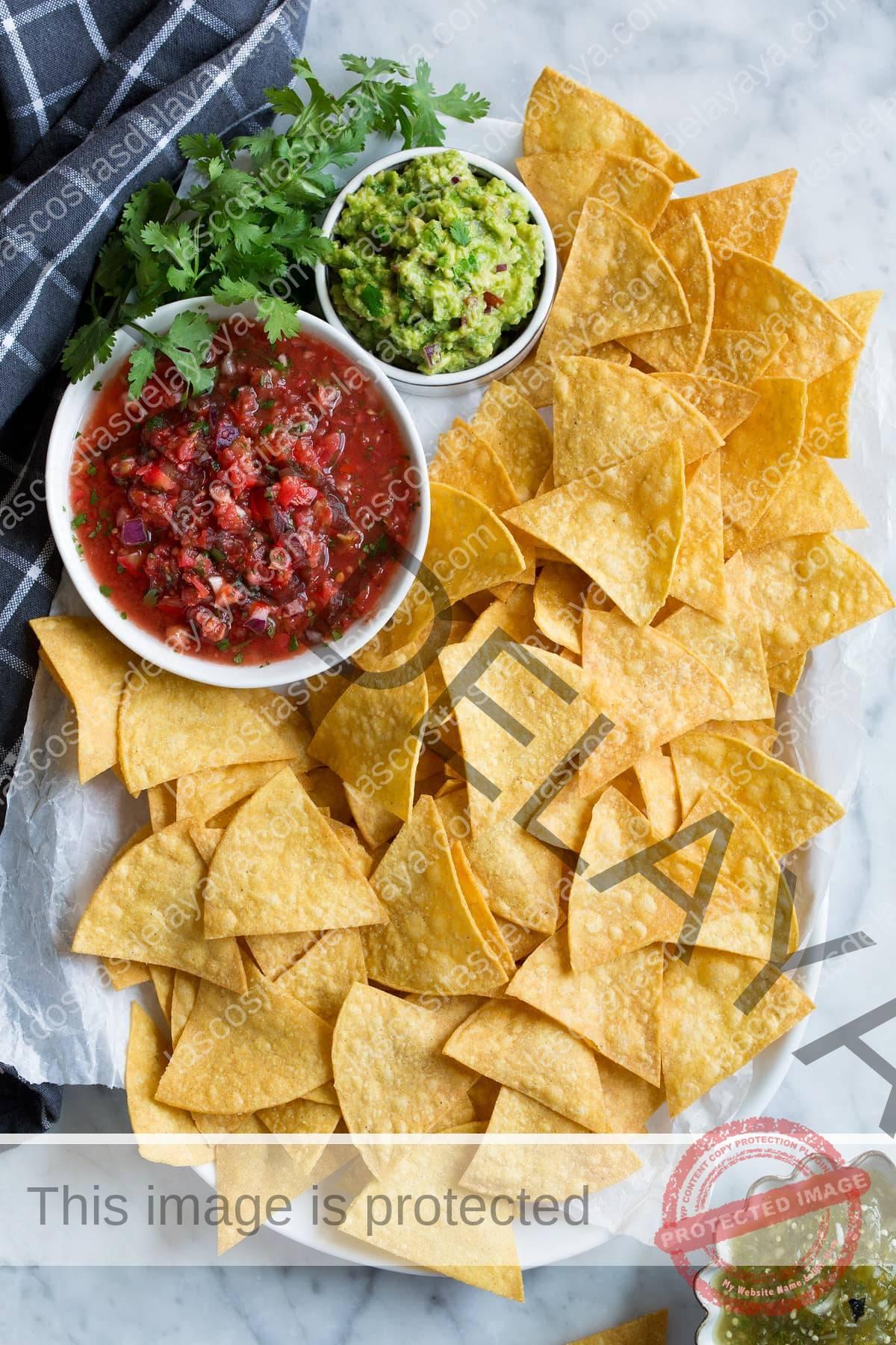Plato lleno de tortillas caseras con acompañamiento de salsa, guacamole y salsa verde.