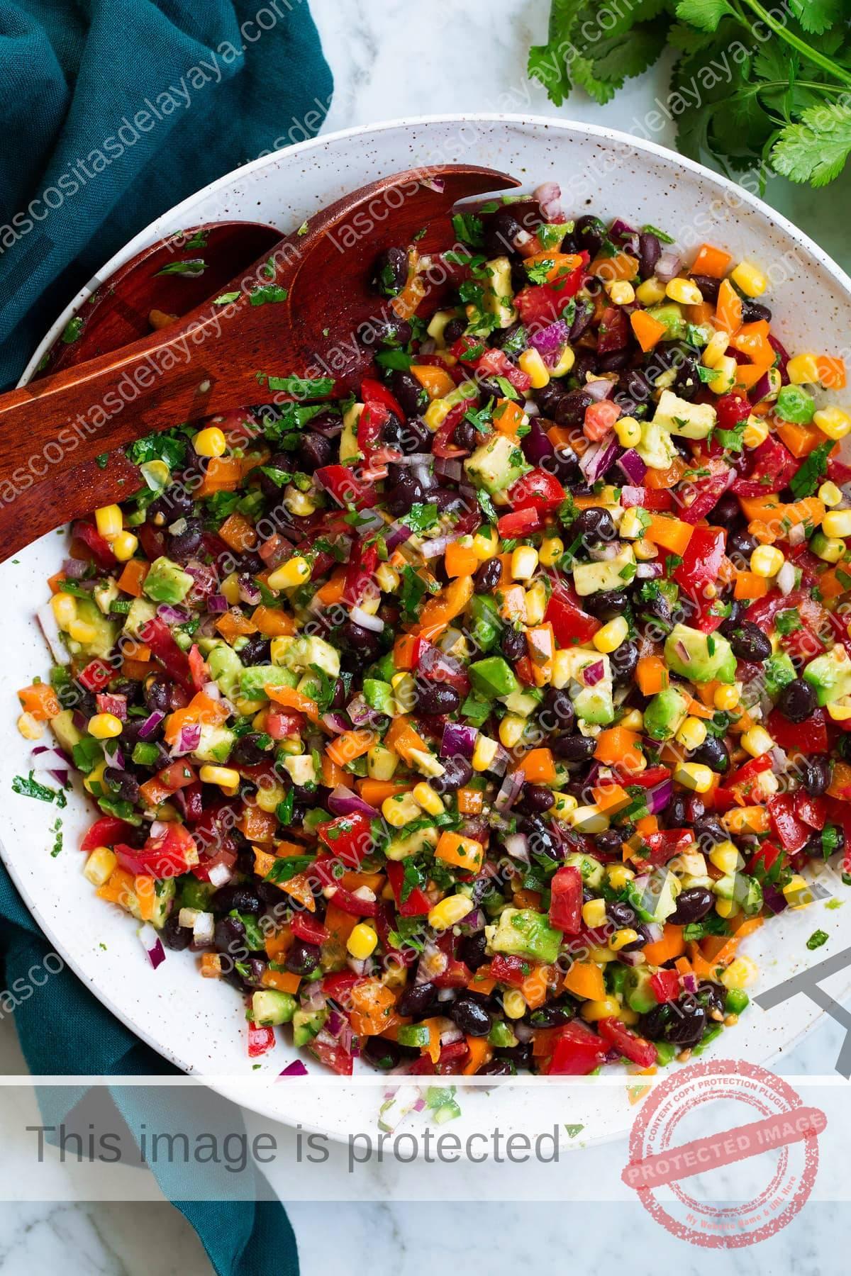 Ensalada de frijoles negros y maíz con salsa de ají, aguacate, tomate y limón y cilantro.