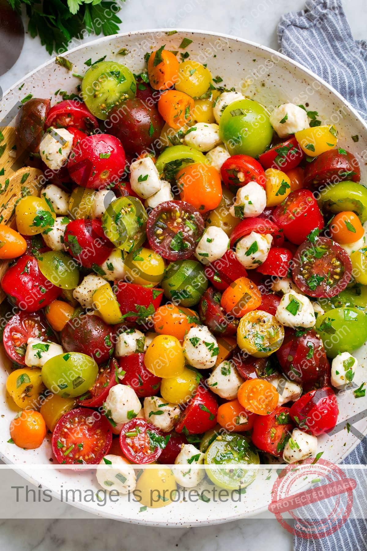 Ensalada de tomate en un tazón blanco. En la ensalada hay tomates cherry y uva multicolores, las perlas de mozzarella y se cubre con un aderezo de hierbas.