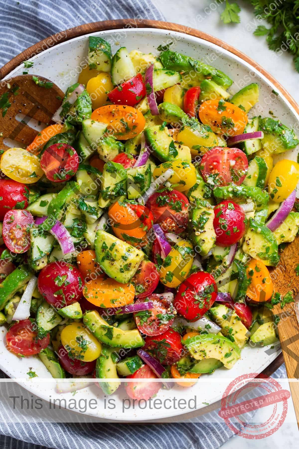 Ensalada de aguacate con aguacate fresco, tomates uva, cebolla morada, pepino y hierbas frescas en un bol.