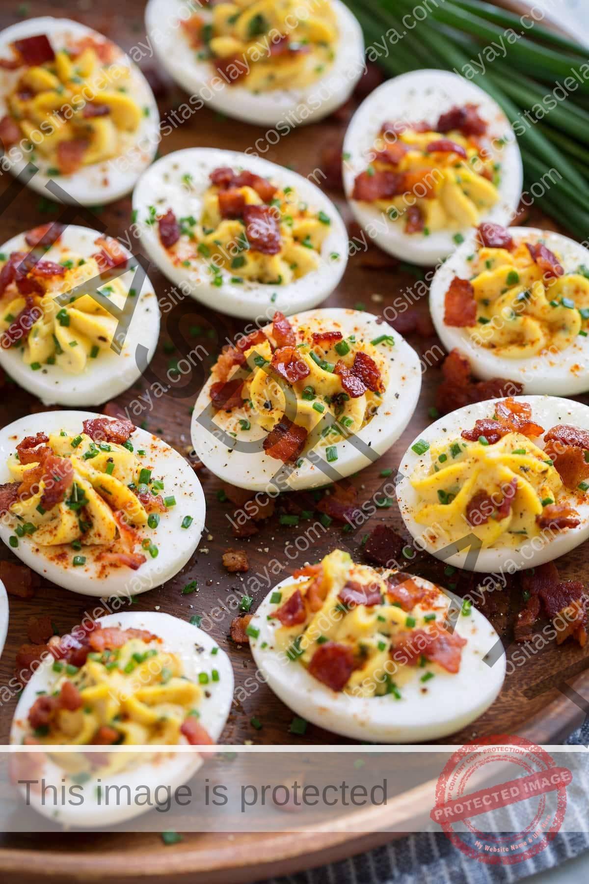 Plato de madera lleno de huevos duros.  Huevos rellenos de mahonesa cremosa y relleno de yema de huevo, acompañados de cebollino y tocino.