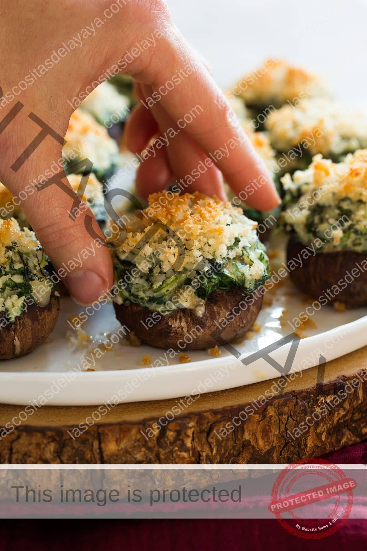 Recogiendo a mano unas setas rellenas de queso crema, quesos rallados y espinacas.