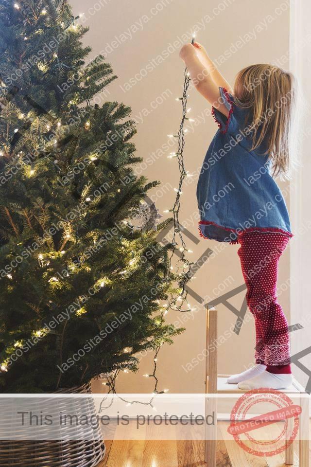 niña caucásica luces colgantes en el árbol de navidad