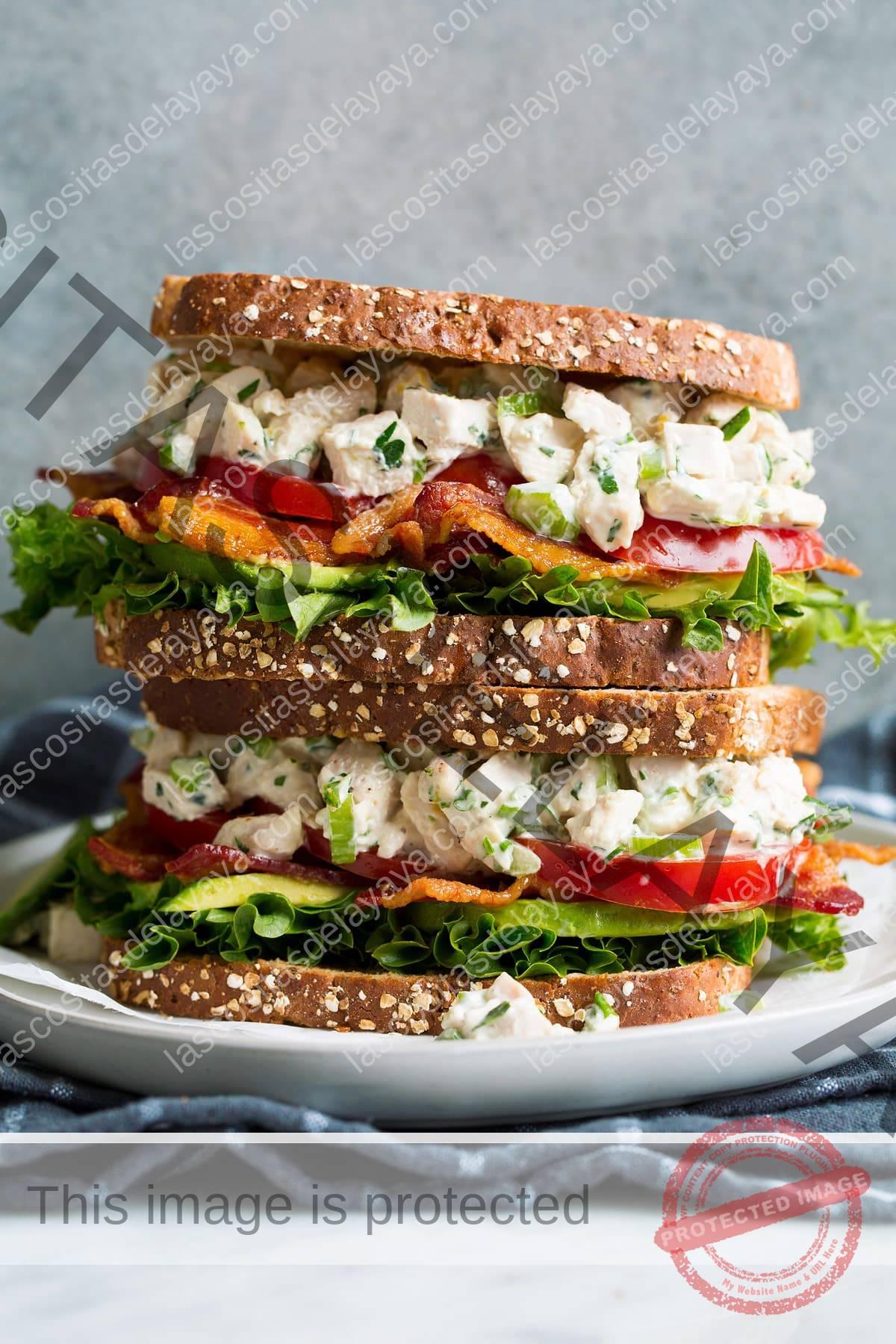 Pila de dos sándwiches de ensalada de pollo en un plato blanco sobre un paño gris oscuro.