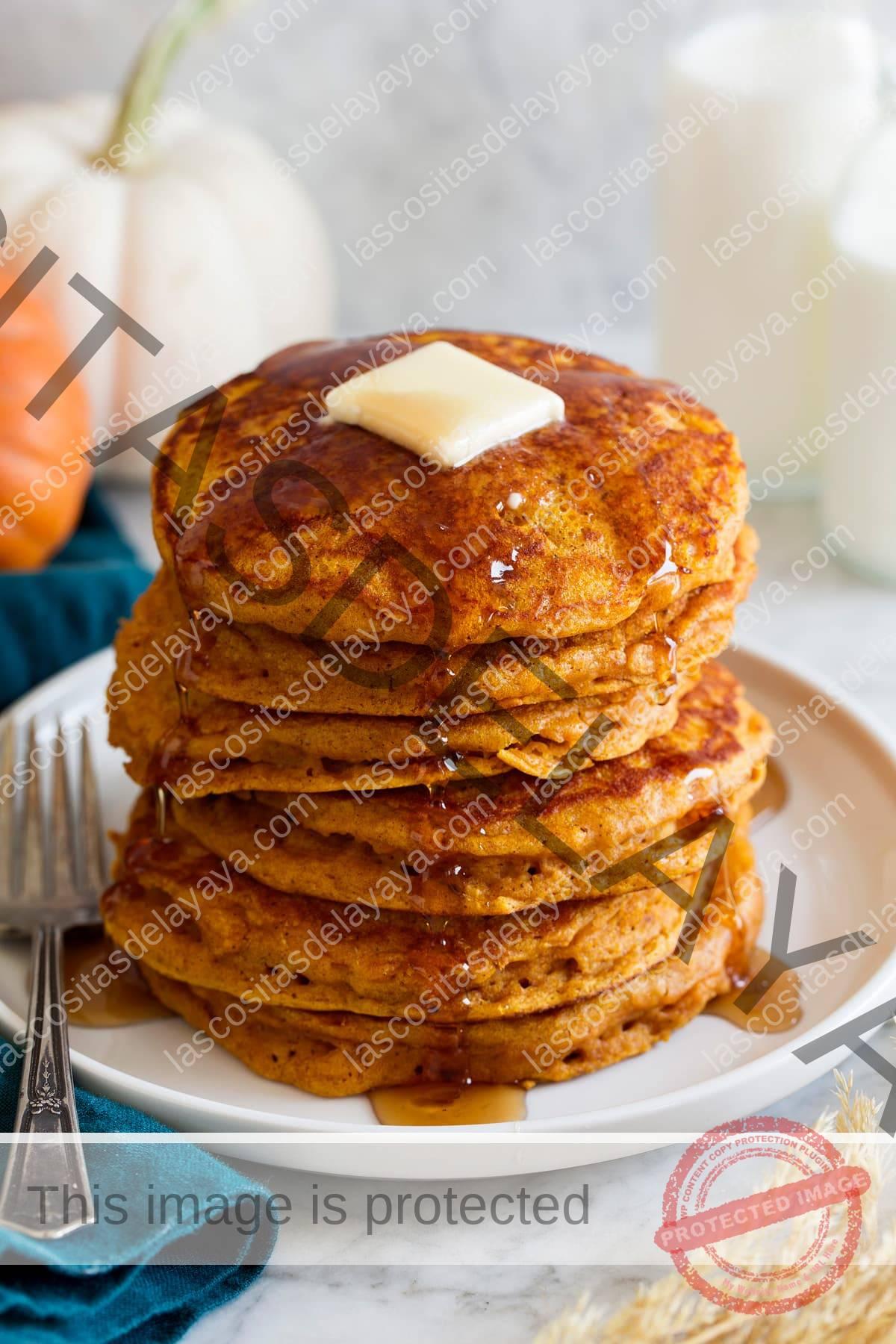 Pila de panqueques de calabaza en una bandeja.  Los panqueques se rocían con jarabe de arce y se cubren con mantequilla.