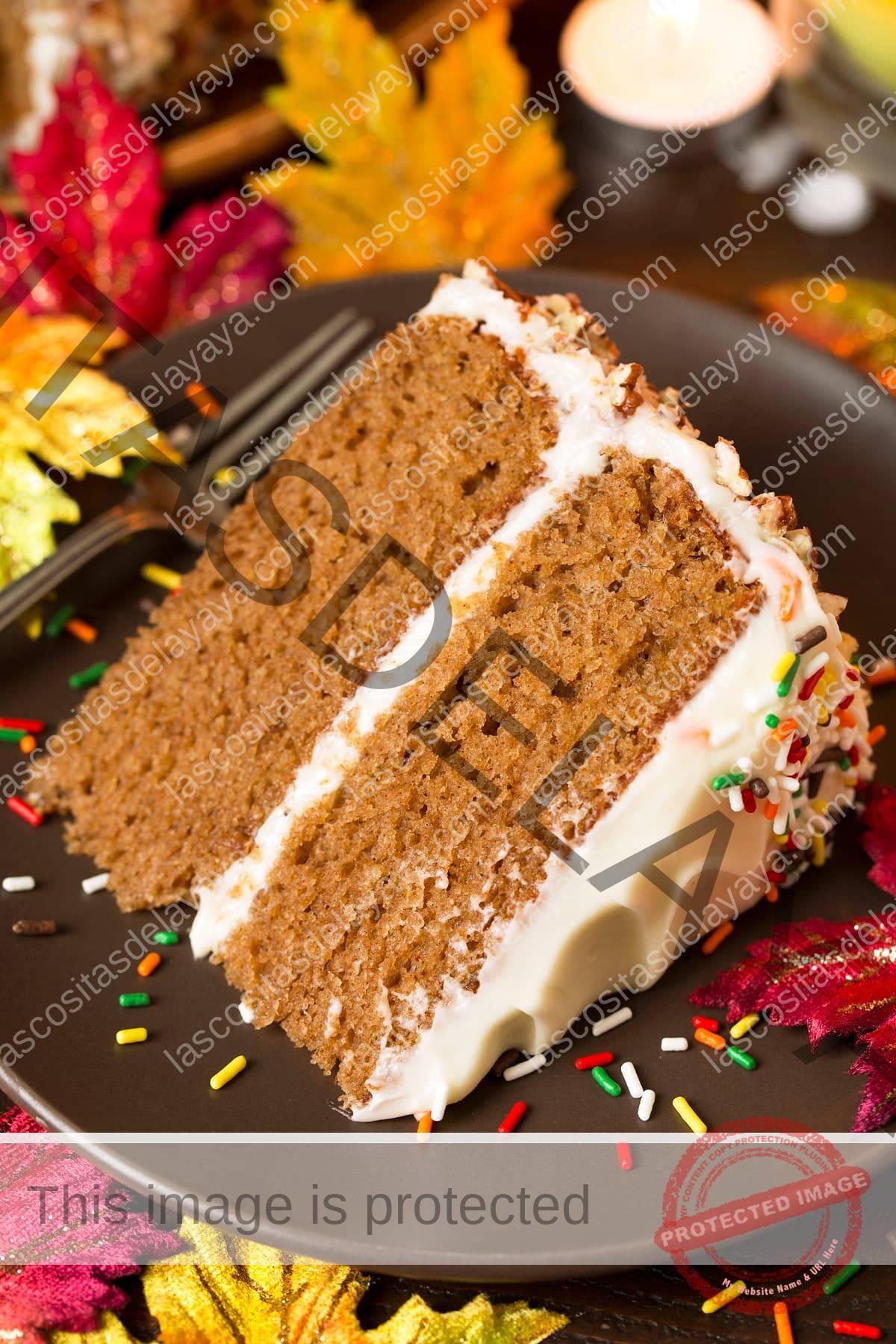Rebanada de pastel de especias con glaseado de queso crema, sobre una placa marrón mate decorada con coloridas hojas de otoño alrededor.