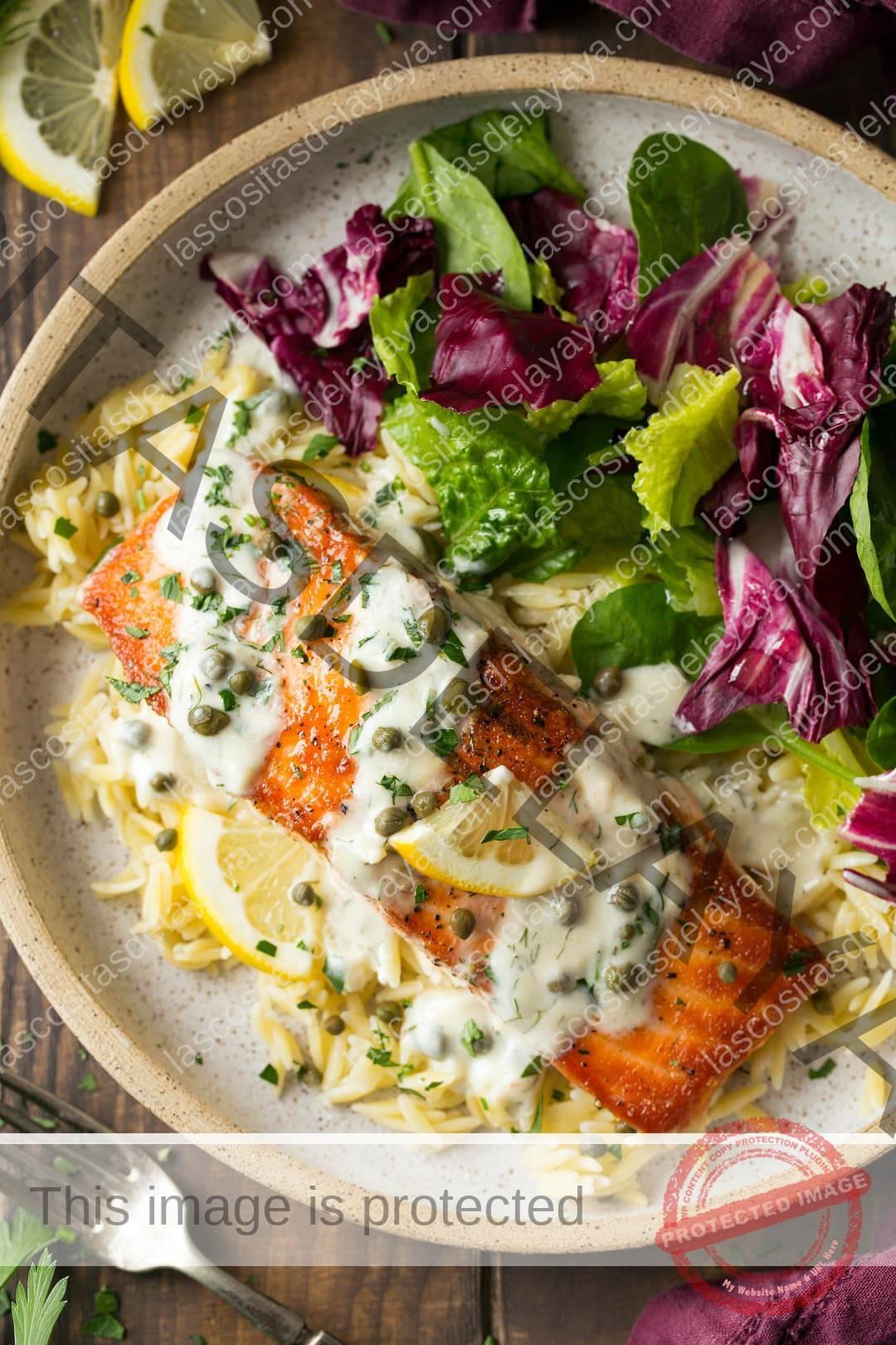 Salmón cocido en la sartén con una cremosa salsa de limón y alcaparras.  Aquí se muestra en un plato para servir con orzo y ensalada.