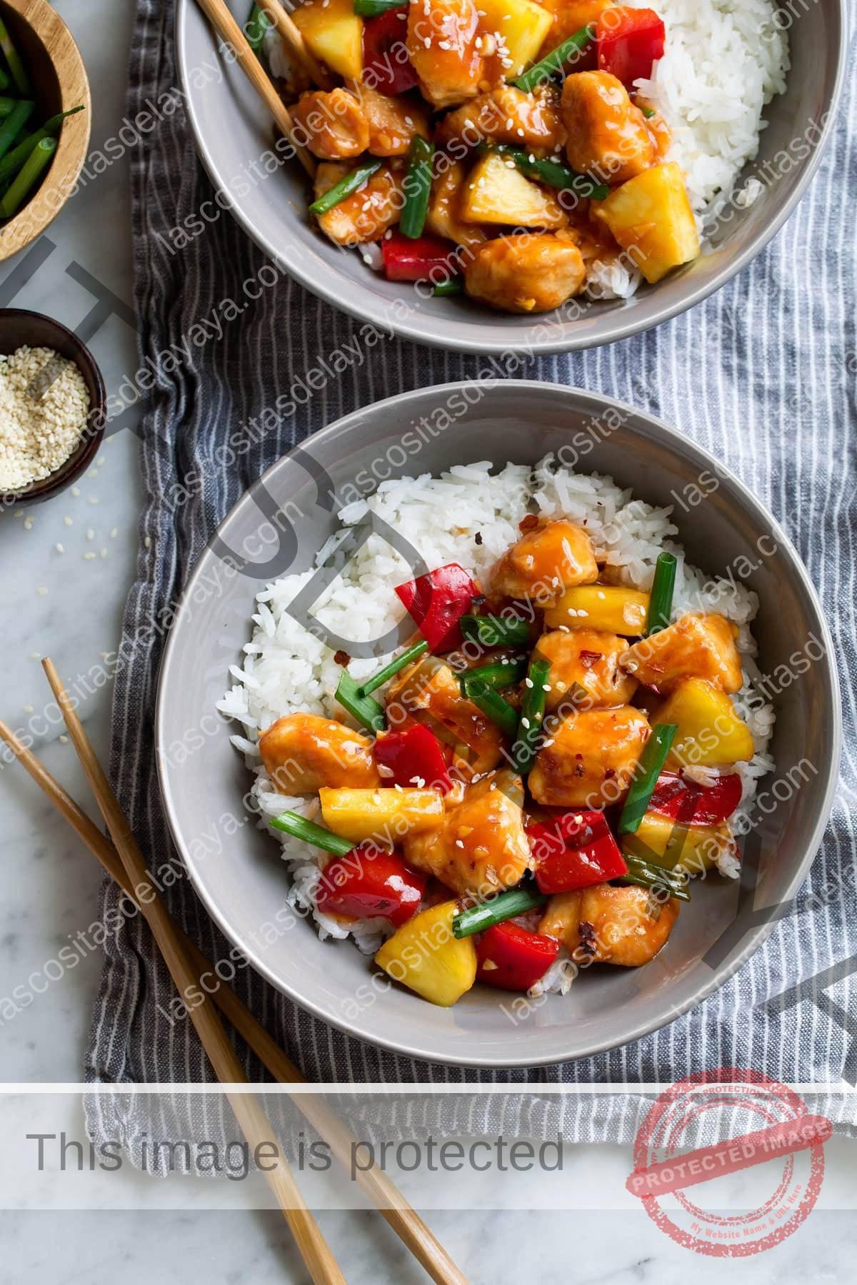 Dos porciones de pollo agridulce sobre cuencos de arroz blanco y gris.