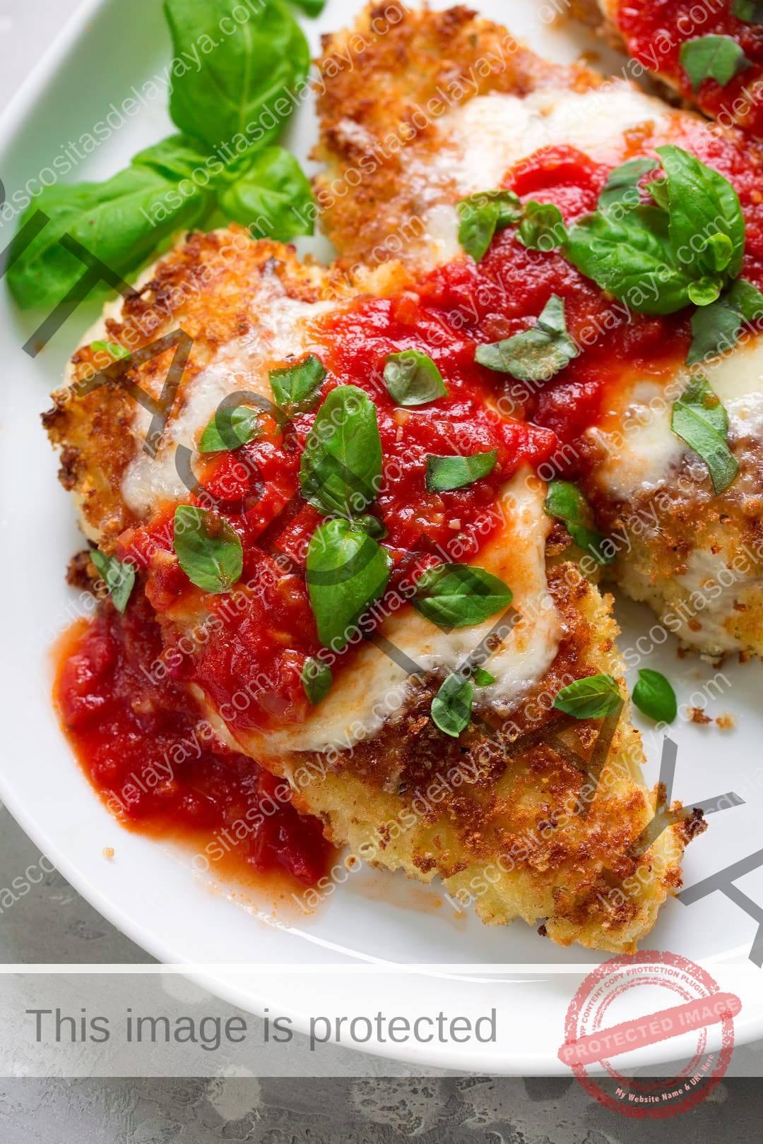 Overhead close-up imagem de duas peças de frango parmesão em um prato de servir branco. O frango é coberto com migalhas de pão Panko douradas, mussarela derretida, molho marinara e manjericão fresco.