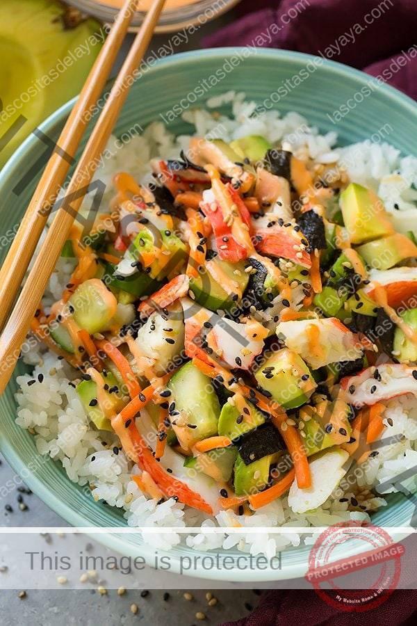 Tazón en capas de ingredientes de California roll, que incluyen arroz para sushi, cangrejo, nori, zanahoria, pepino, aguacate, mayonesa picante y semillas de sésamo.