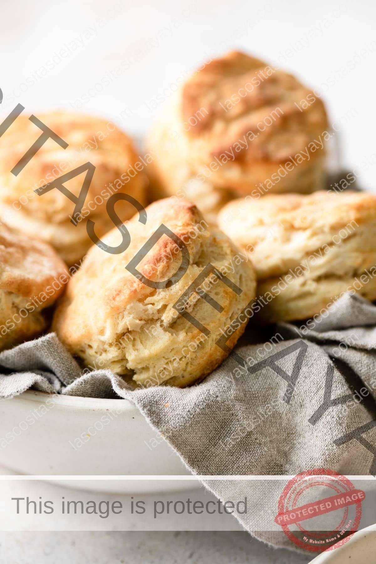Galletas altas y escamosas apiladas en un recipiente con una toalla de cocina gris.
