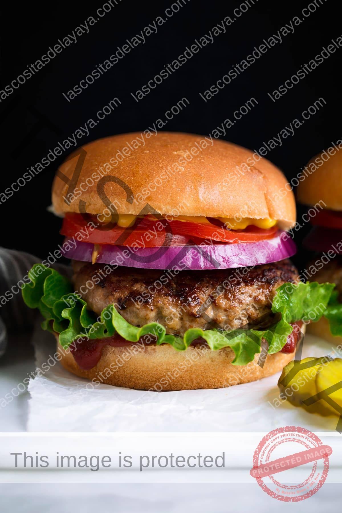 Hamburguesa de pavo con capas de pan, salsa de tomate, lechuga, hamburguesa de pavo, cebolla morada, tomate y mostaza amarilla.  Servido con encurtidos en bandeja blanca.
