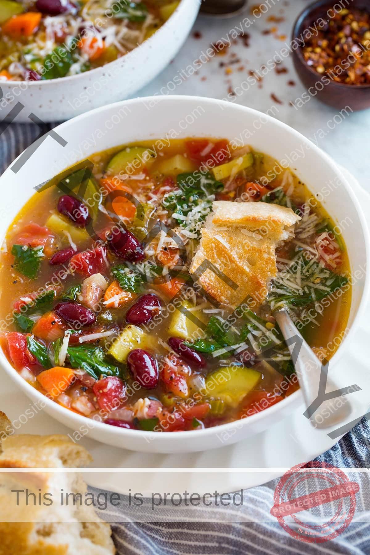 Imagen de una porción de sopa minestrone en un recipiente blanco sobre un plato blanco.  La sopa se adorna con parmesano y se cubre con pan.