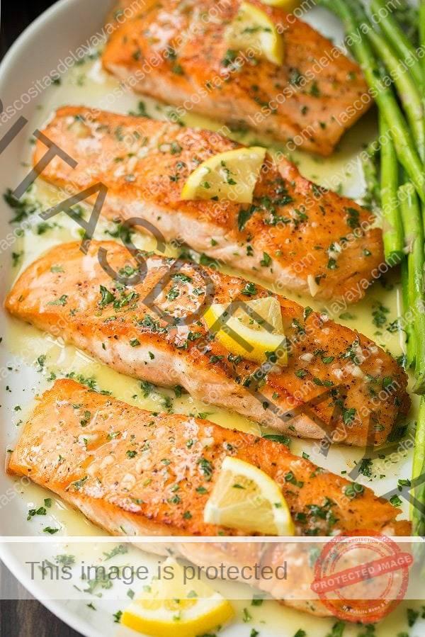 Filetes de salmón a la plancha en bandeja con mantequilla y salsa de ajo y limón.  Servido con una guarnición de espárragos.