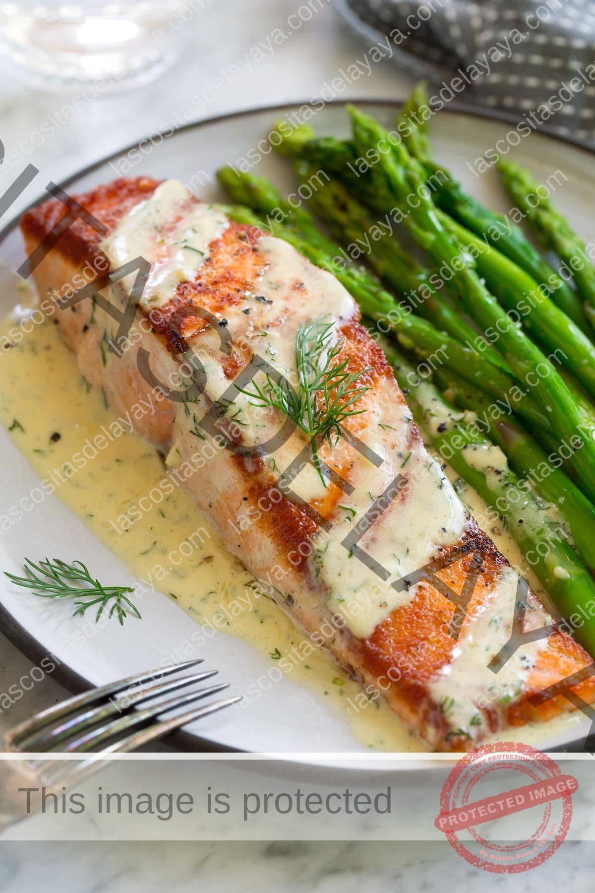 Una sola sartén de filete de salmón a la plancha en un plato blanco.  El salmón se rocía con una salsa cremosa de mostaza y se espolvorea con eneldo.  Se sirve acompañado de espárragos.