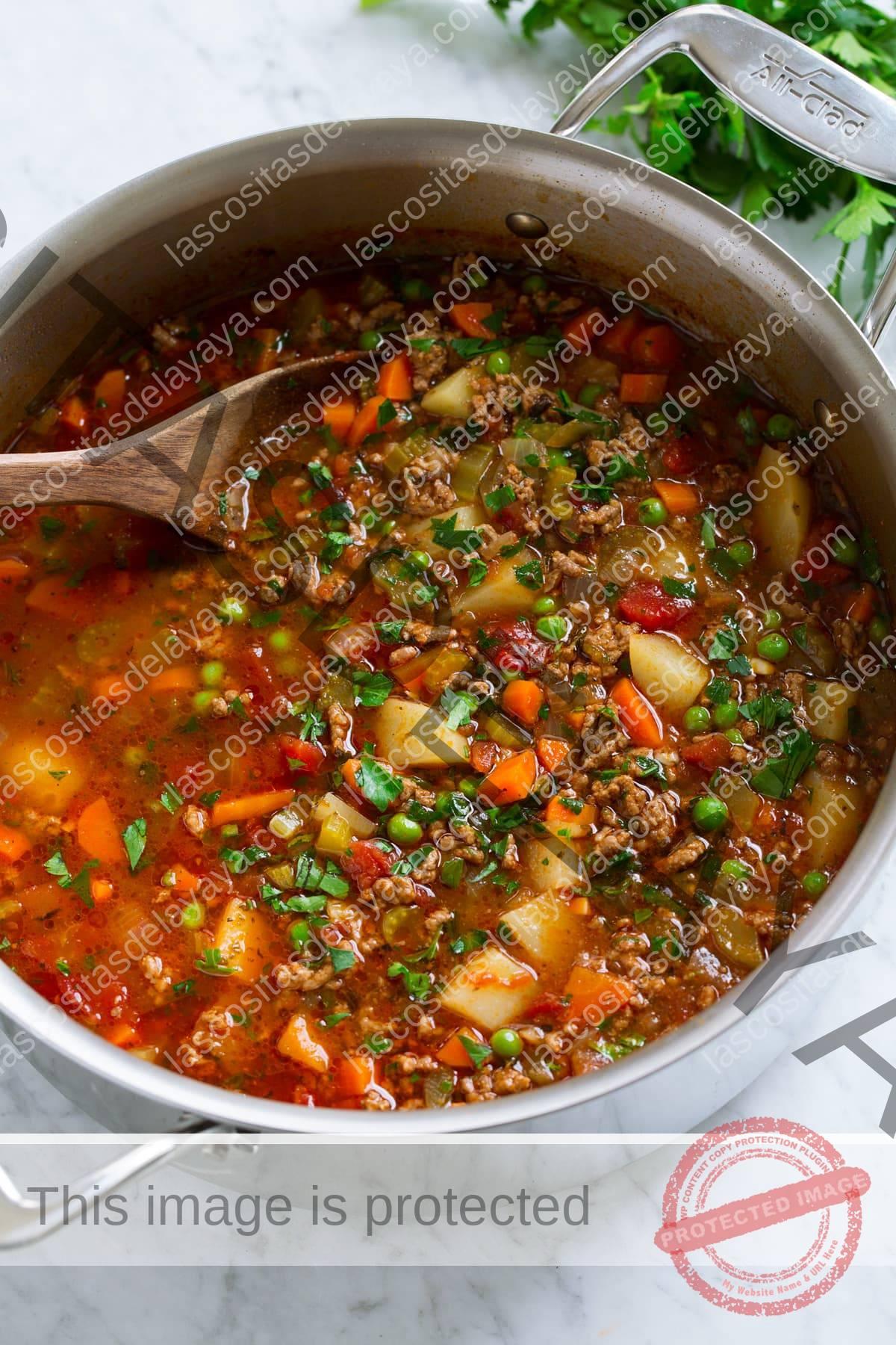 Sartén de acero inoxidable llena de sopa de hamburguesa picada con patatas, zanahorias, guisantes, apio, tomates, hierbas y caldo