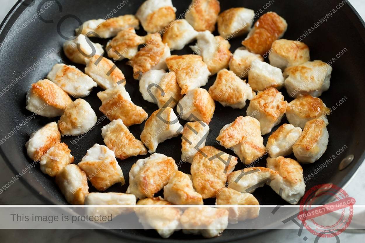 Tostar trozos de pechuga de pollo en una sartén