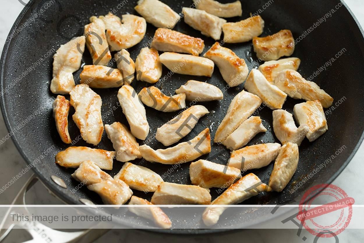 Trozos de pollo en la sartén para chow mein.