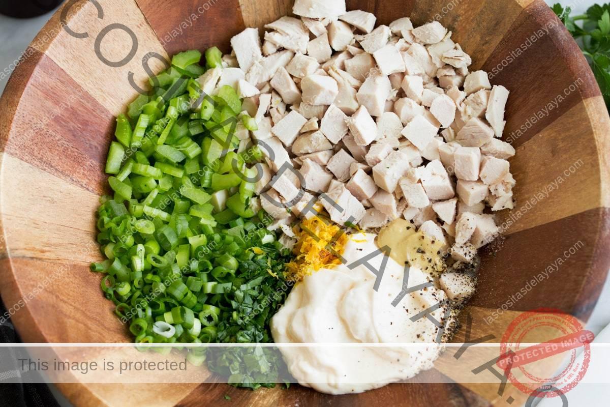 Mostrando cómo hacer ensalada de pollo echando trozos de pechuga de pollo, mayonesa, dijon, limón, apio, cebollino, perejil en un tazón de madera.