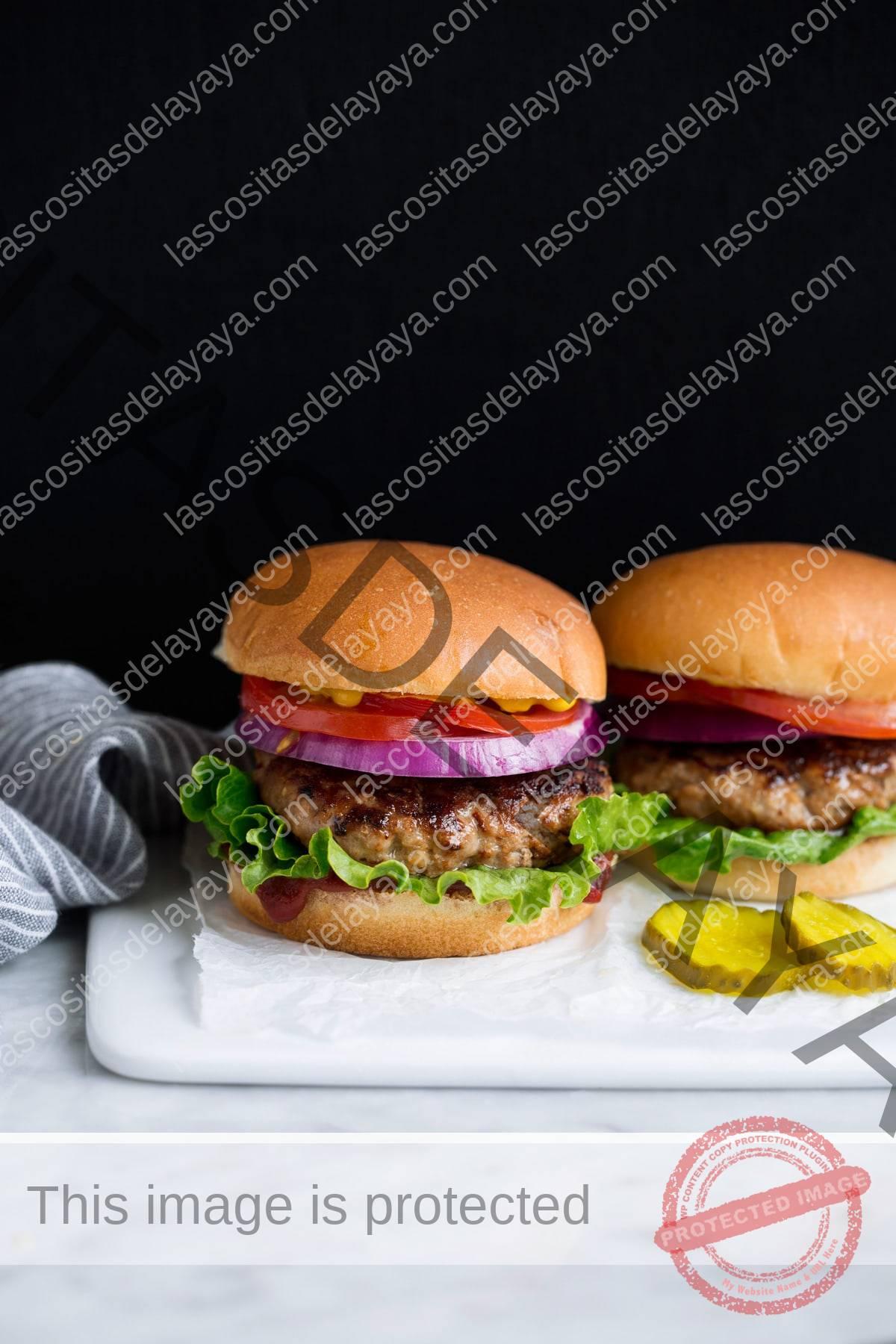 Dos hamburguesas de pavo en un plato blanco.