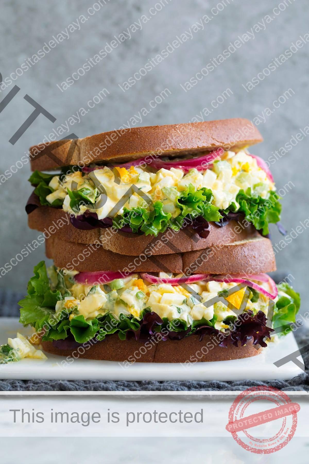 Pila de dos sándwiches de ensalada de huevo en un plato blanco sentado sobre mármol con un fondo gris.