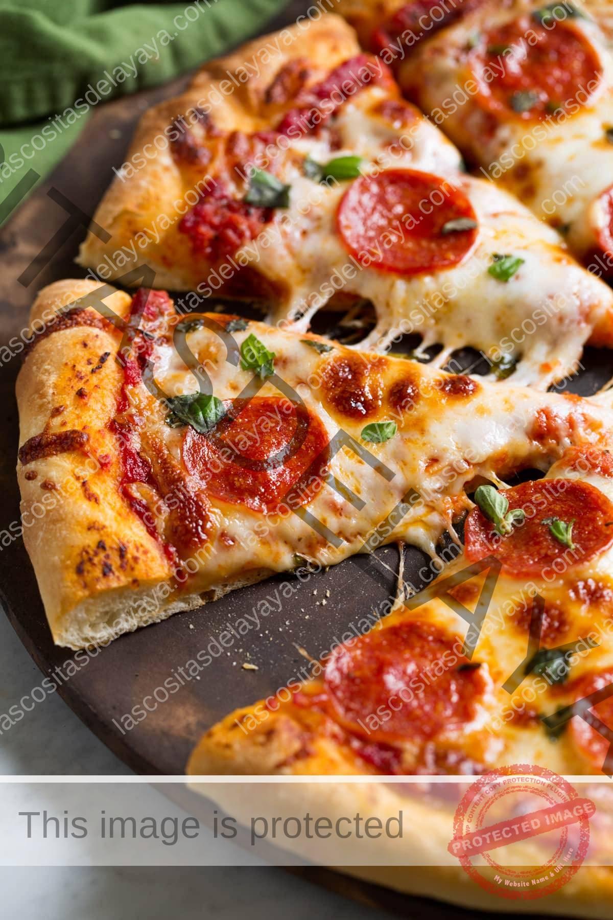 Fatias de pizza de calabresa feita com receita de massa de pizza caseira.