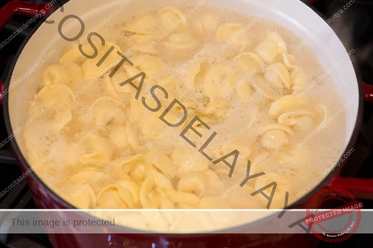 Tortellini hirviendo en la mezcla de caldo para hacer sopa de tortellini.