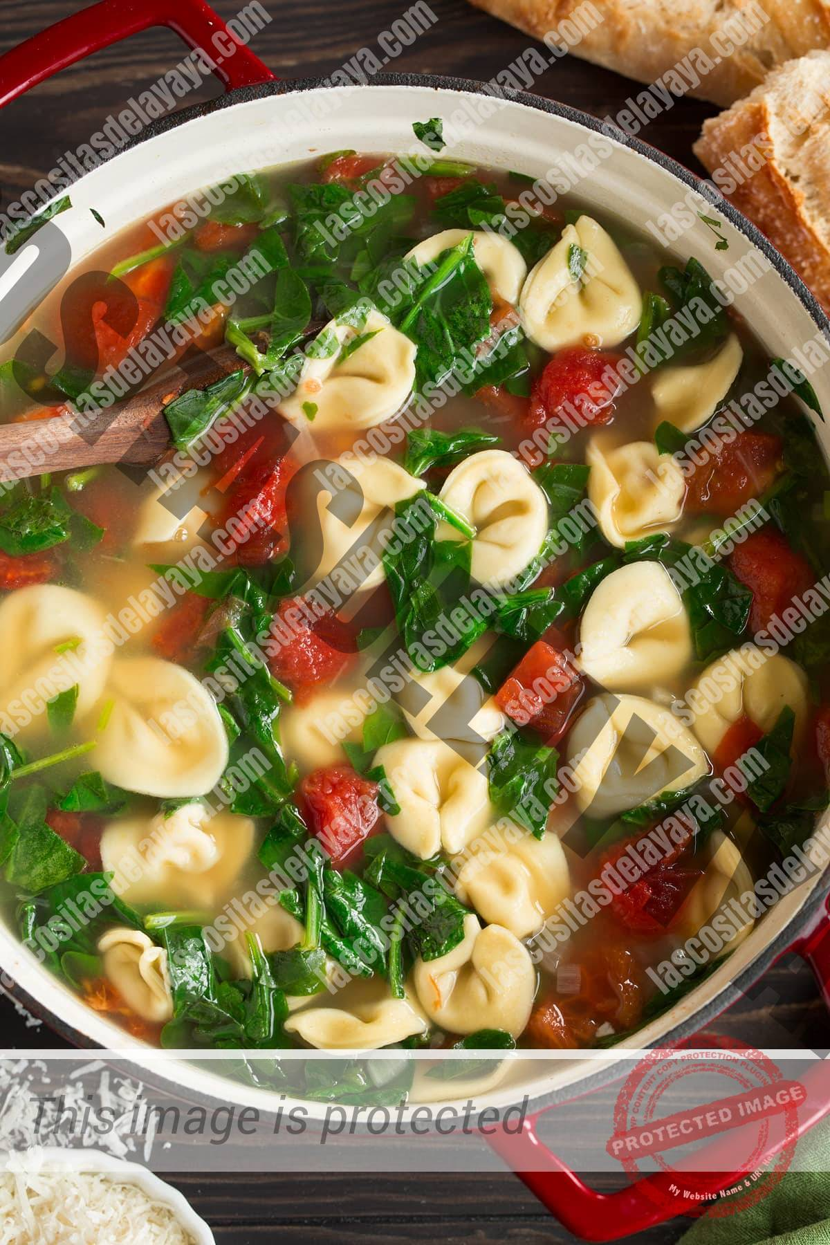 Imagen aérea de sopa de tortellini en una sartén roja grande.
